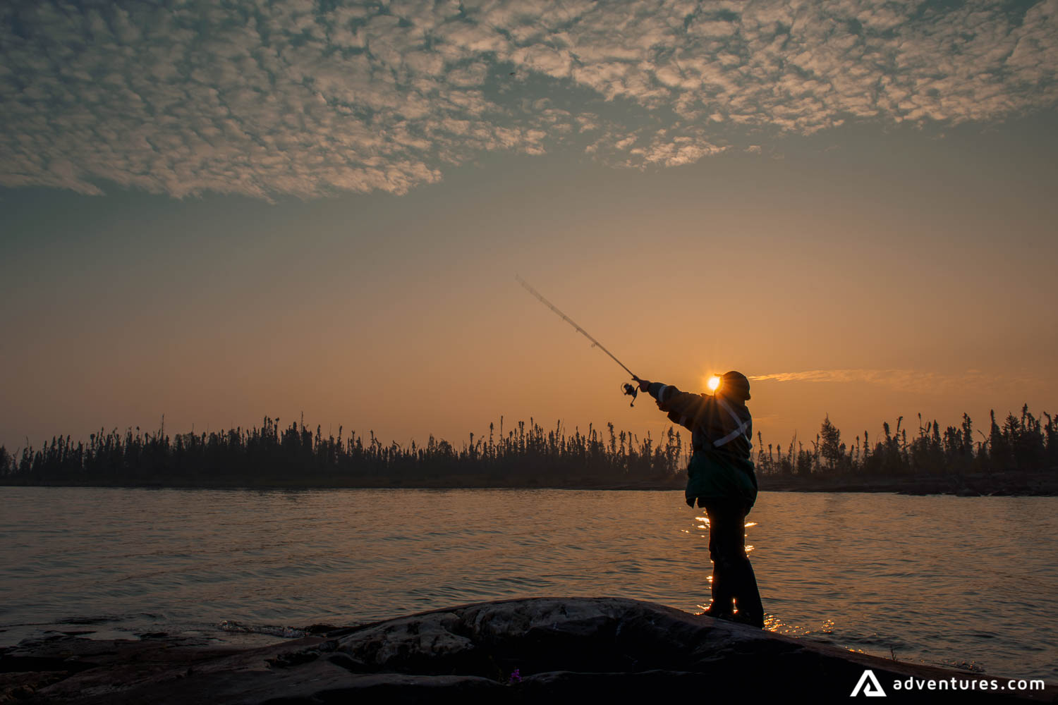 Man fly fishing at sunset