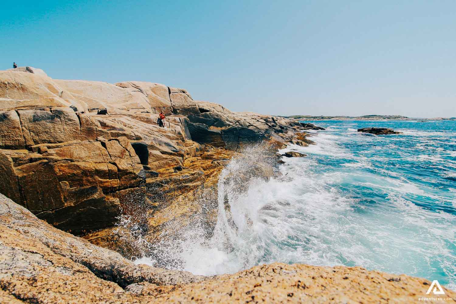 Waves crash into the cliff