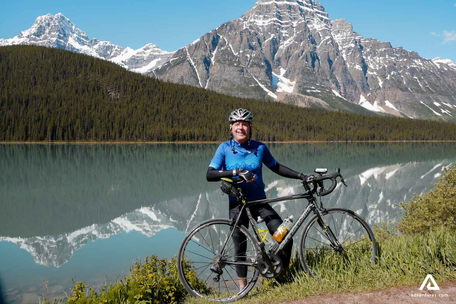 Man with a bicycle in rocky mountains