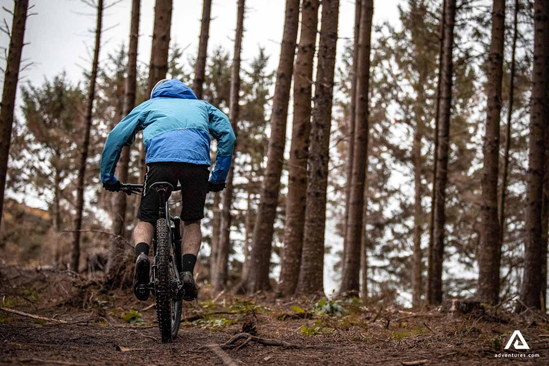 Man mountain biking rear view
