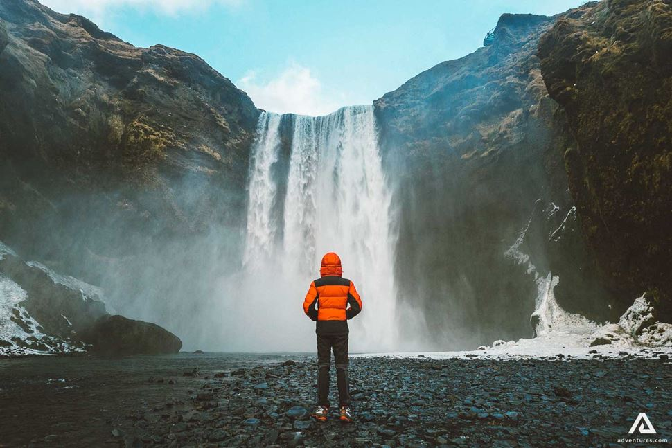 Man Standing In Front Of Skogafoss Waterfall