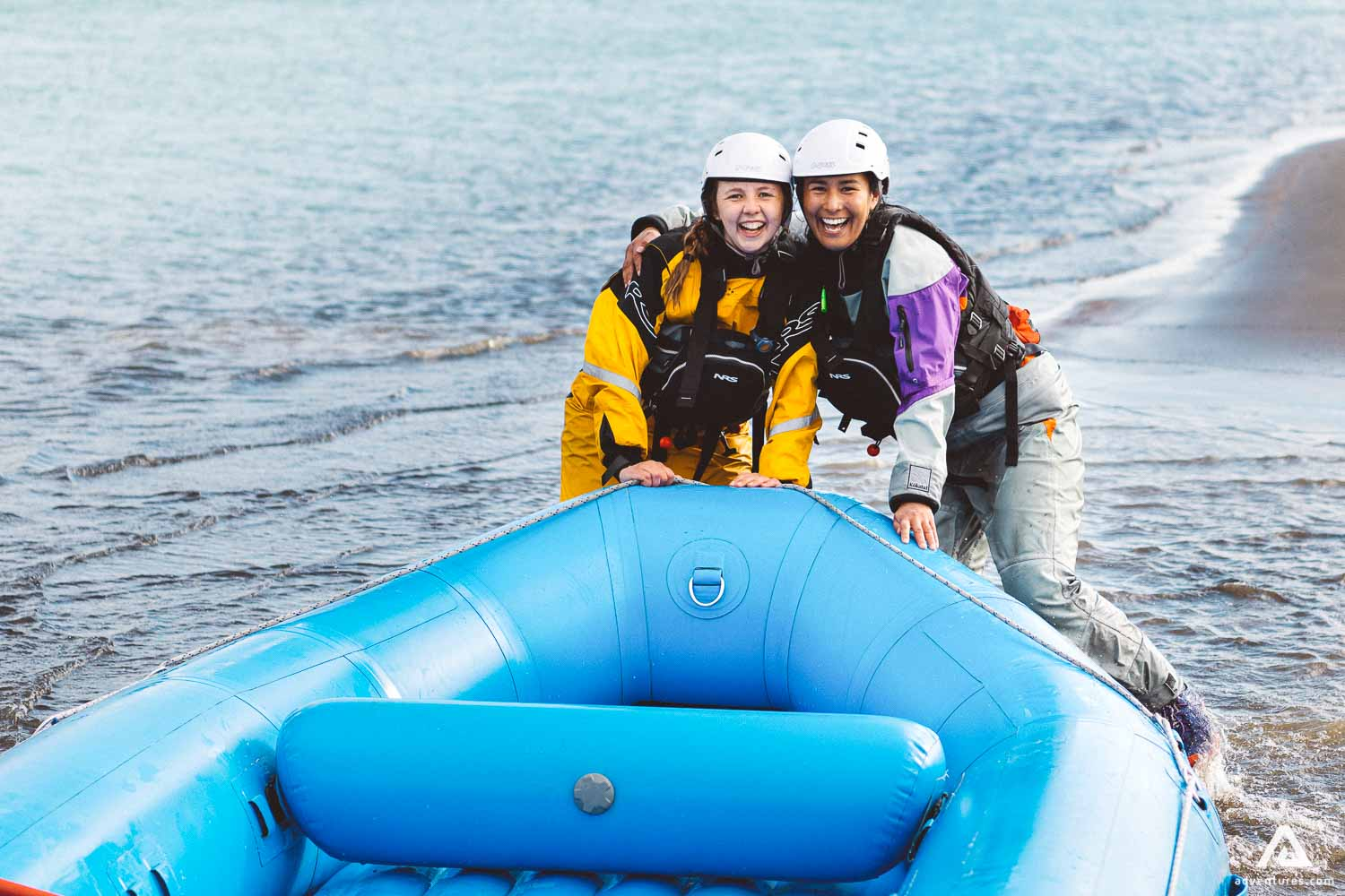 Two Girls Are Smiling Next To Rafting Boat
