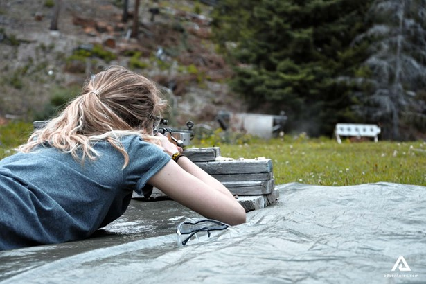 Girl lying down and shooting with a rifle
