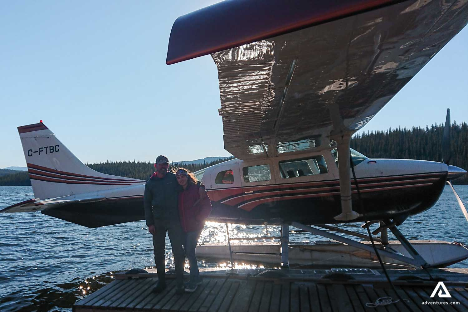 Couple near bushplane on the lake