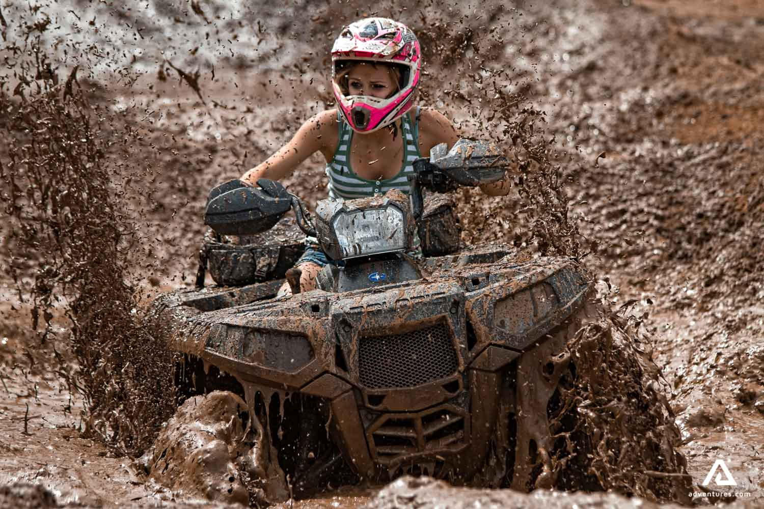 Girl riding quad bike in the mud