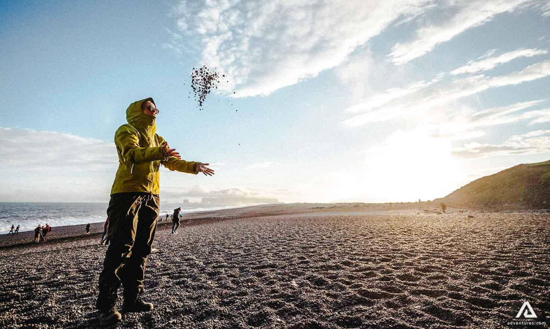 Woman throwing rocks on the beach