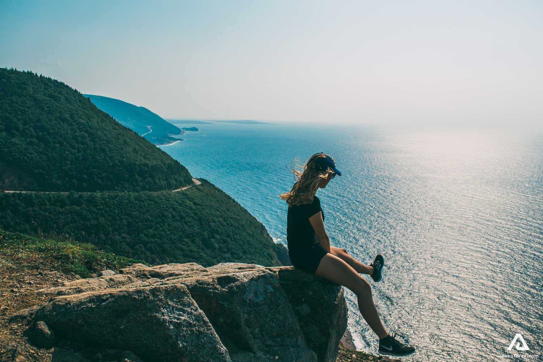Girl Sitting on the Edge of Cliff near Blue Sea