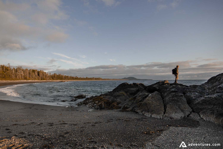 Man standing on rocks of the black sand beach