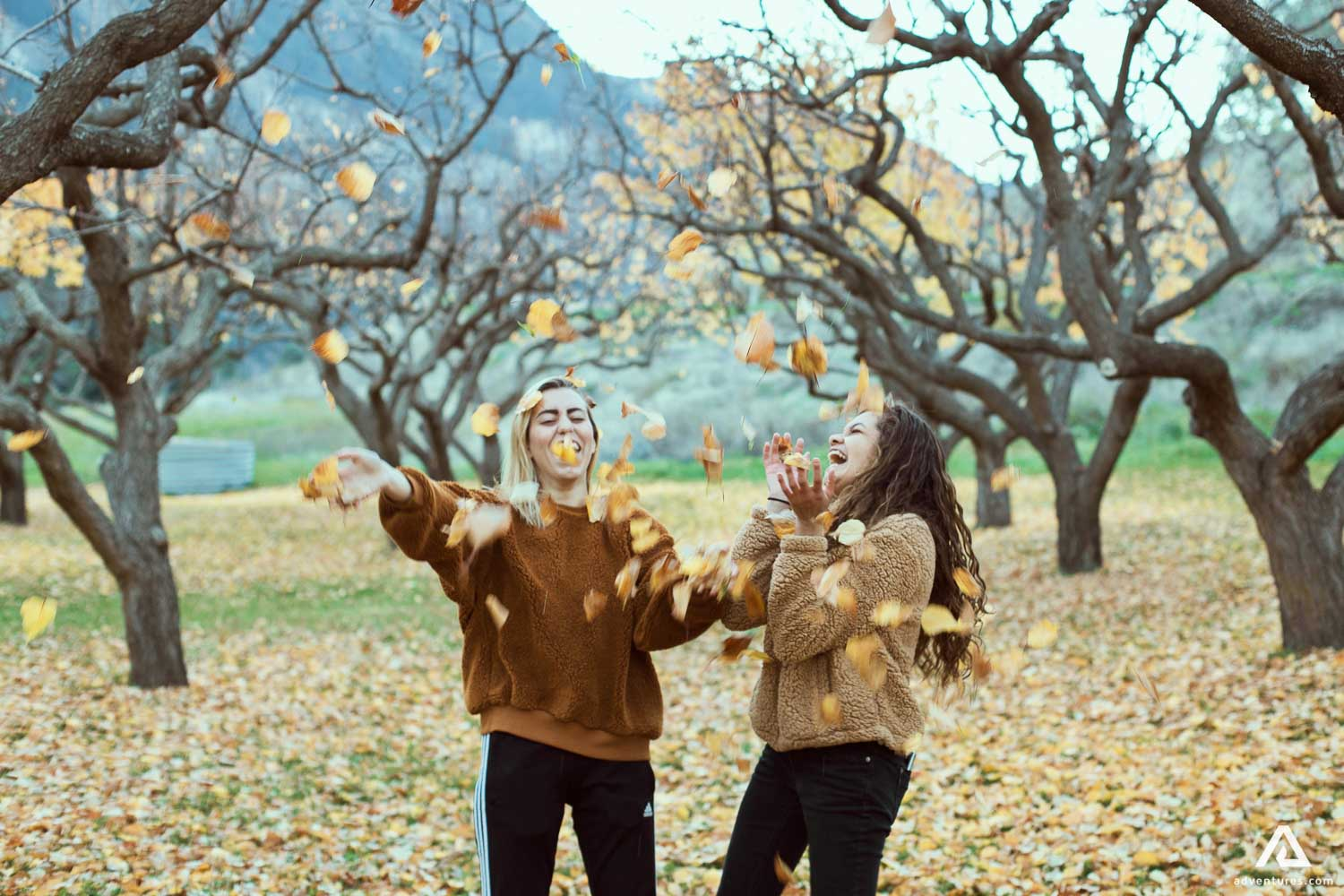 Autumn leaves falling on happy girls