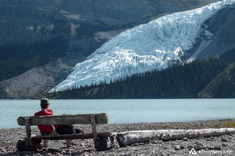 Man sits on bench beside lake