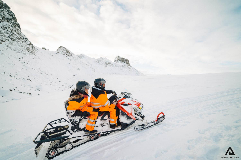 Couple riding snowmobile