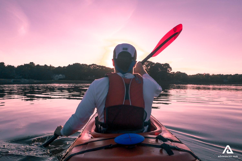 Man kayaking back view